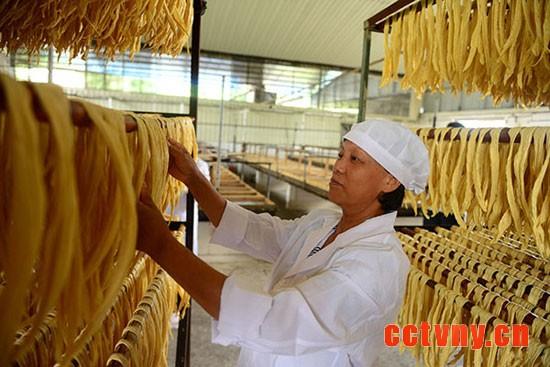 5月16日,广西昭平县木格乡一家生产腐竹的企业工人在摊晾腐竹。